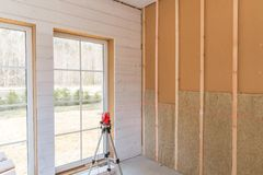 Construction worker thermally insulating eco-wood frame house with wood fiber plates and heat-isolating natural hemp. Material. Finishing the walls with a white stock photos