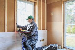 Construction worker thermally insulating eco wooden frame house. The worker makes finishing works of walls with a white wooden board. Building heat-insulating stock photography