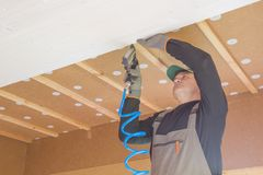 Construction worker thermally insulating eco wooden frame house Stock Photos