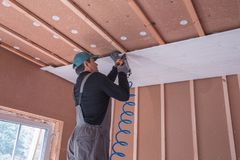 Construction worker thermally insulating eco wooden frame house Stock Photo