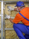 Thermal insulation work. Construction worker thermally insulating house attic with mineral wool Stock Photography