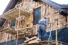 Construction worker thermally insulating house facade with glass wool. Stock Photo
