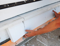 Construction worker thermally insulating house foundation walls with styrofoam boards. Close up on foundation insullation Stock Photos