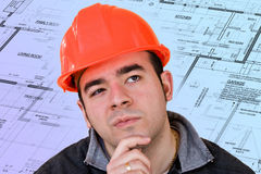 Construction Worker Thinking. A construction worker or architect wearing a hard hat has a contemplative look on his face with generic blueprints in the Royalty Free Stock Photo