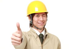 Construction worker with thumbs up gesture. Studio shot of young Japanese man on white background Stock Photography