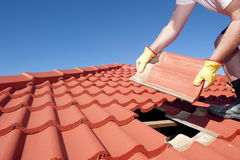 Construction worker tile roofing repair. Roof repair, worker with yellow gloves replacing red tiles or shingles on house with blue sky as background and copy