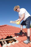 Construction worker tile roofing repairs stock photography