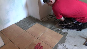 Construction worker tiler place floor tiles. Right side sliding Royalty Free Stock Images