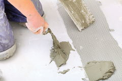 Construction worker is tiling at home, tile floor adhesive. Home improvement, renovation - construction worker tiler is tiling, ceramic tile floor adhesive Royalty Free Stock Image