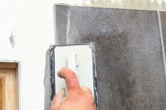 Construction worker is tiling at home, tile floor adhesive Stock Images