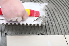 Construction worker is tiling at home, tile floor adhesive. Home improvement, renovation - construction worker tiler is tiling, ceramic tile floor adhesive Stock Image