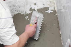 Construction worker is tiling at home tile floor adhesive Royalty Free Stock Images