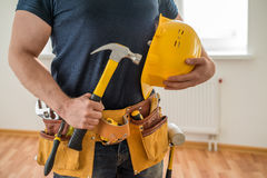 Construction worker with tool belt and hammer. Construction worker with tool belt, helmet and hammer stock photo