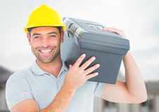Construction Worker with tool box in front of construction site. Digital composite of Construction Worker with tool box in front of construction site Royalty Free Stock Photo