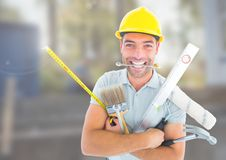 Construction Worker with tools in front of construction site. Digital composite of Construction Worker with tools in front of construction site Royalty Free Stock Images