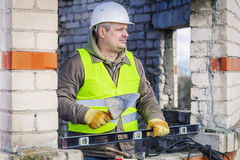 Construction worker with trowel and level near wall Royalty Free Stock Image