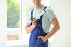Construction worker in uniform with window sealant. Indoors Stock Image