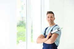 Construction worker in uniform with window sealant. Indoors Royalty Free Stock Photography
