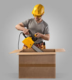 Construction worker unpacks the box with delivery chain saw Stock Image
