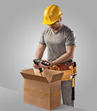 Construction worker unpacks the box with delivery drill Stock Image