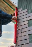 Construction worker use a spirit level to check decorative tiles on the facade of the building.  Royalty Free Stock Photography