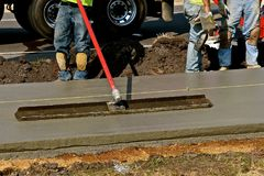 Worker using a bull float on sidewalk project Stock Photos