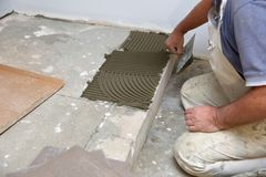 The construction worker evenly spreads the surface of the stairs with cement adhesive mass using a special hand tool. stock photo