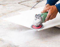A construction worker using an angle grinder cutting board Stock Photography