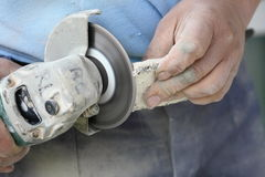 Construction worker using an angle grinder cutting tile Royalty Free Stock Images