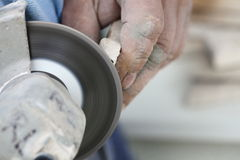 Construction worker using an angle grinder cutting tile Royalty Free Stock Image