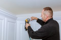 Construction worker using brad nail air gun to Crown Moulding on white kitchen wall cabinets framing trim,. With the all power tools Stock Photography