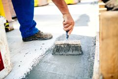 Construction worker using brush and primer for hydroisolating and waterproofing house Stock Image