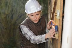 Construction worker using building leve. Female royalty free stock image