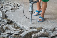 Construction worker using concrete drilling machine in construct Stock Photos