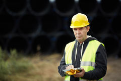 Construction worker using digital tablet. Builder with small computer and gloves, selective focus on face Royalty Free Stock Photography