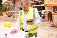 Construction Worker Using Digital Tablet On Building Site Stock Image