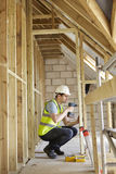 Construction Worker Using Drill On House Build. Construction Worker Using Drill On Wooden Frame Of House Stock Images
