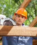 Construction Worker Using Electric Saw On Timber. Male construction worker using electric saw on timber frame at site Royalty Free Stock Image