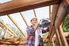 Construction Worker Using Electric Saw On Wooden Stock Photo