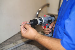 Construction worker using an electric screwdriver. Stock Image