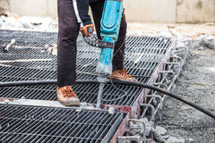 Construction worker using  jackhammer drill floor cement. On site construction Stock Photography