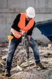 Construction worker using a jackhammer. Male construction worker using a jackhammer on construction site Royalty Free Stock Photography
