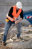 Construction worker using jackhammer. Male construction worker using jackhammer. Vertical shot Royalty Free Stock Image