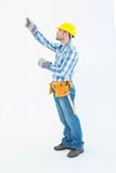 Construction worker using measure tape. Full length of construction worker using measure tape against white background Royalty Free Stock Image