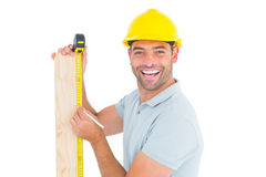 Construction worker using measure tape to mark on plank. Male construction worker using measure tape to mark on wooden plank on white background royalty free stock images