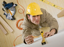 Construction worker using measuring tape. Construction worker in hard-hat using measuring tape for project royalty free stock images