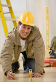 Construction worker using measuring tape. Construction worker in hard-hat kneeling and using measuring tape to mark floor royalty free stock image