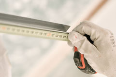 Construction worker using measuring tape. Close up royalty free stock image