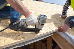 Construction worker using nail gun to nail Oriented Strand Board osb sheeting on roof of a new home. Construction worker using nail gun to nail Oriented Strand Royalty Free Stock Images