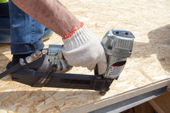 Construction worker using nail gun to nail Oriented Strand Board osb sheeting on roof of a new home. Stock Photos